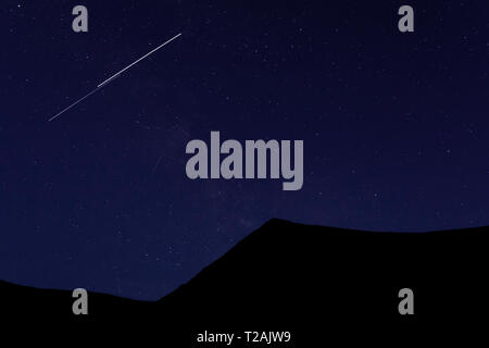 Shooting star above silhouette of mountain - Stock Image