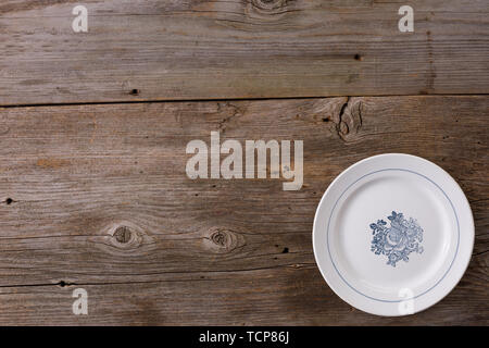 Empty plate with spoon and fork on wooden background. Flat lay. Place under your text. Cutlery. - Stock Image