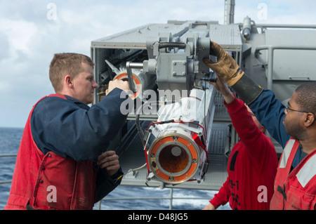 Sailors load a Sea Sparrow Missile. - Stock Image