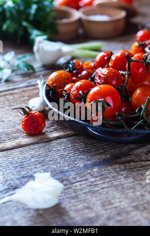 Roasted with herbs organic homegrown cherry tomatoes in cast iron skillet,  garlic and fresh parsley on rustic  wooden table, plant based food, close - Stock Image