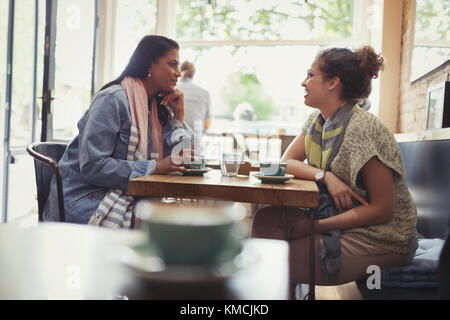 Women friends drinking coffee and talking at cafe table - Stock Image