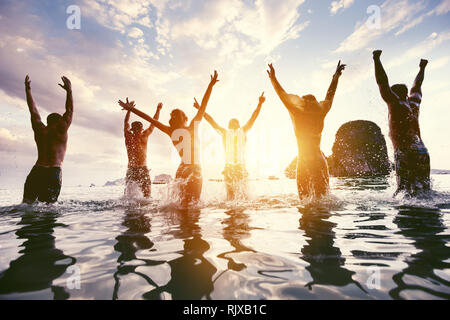 Group of happy friends jumps and having fun at sunset sea beach. Tropical travel concept with peoples silhouettes - Stock Image