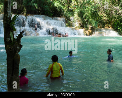 Tourists cooling off in clear water pool of  three tiered Tat Kuang Si Waterfalls in Kuang Si Waterfalls Park near Luang Prabang Laos Asia - Stock Image