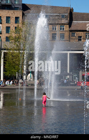 Young child playing in the fountain in Centenary Square, Bradford, West Yorkshire - Stock Image