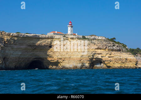 A view of Alfanzina Lighthouse above the rugged limestone cliffs and grottos along the Algarve coast in Portugal. - Stock Image