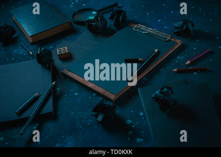 Science and research concept with a clipboard, black paper notes and a magnifying glass. Starry sky background. Dark business concept with copy space. - Stock Image