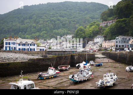 The village of Lynmouth, North Devon - view of harbour at low tide with boats, houses and hillside beyond. - Stock Image