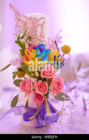 Floral arrangement with fancy rainbow colored roses as beautiful decor for table centerpieces at weddings or formal events - Stock Image