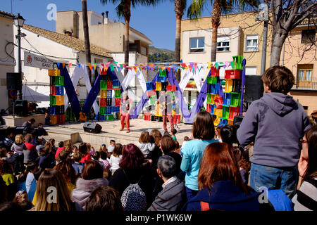 Two comedy entertainers on an outdoor stage watched by a crowd during a Spanish Fiesta - Stock Image