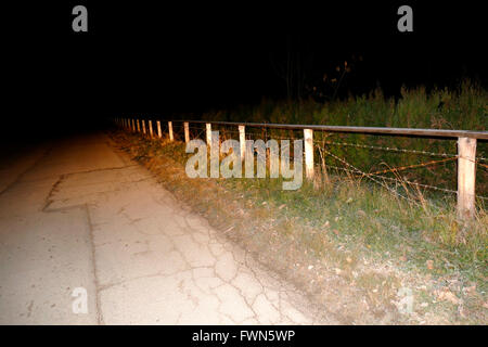 Night time photo of a fence, headlights flash. - Stock Image