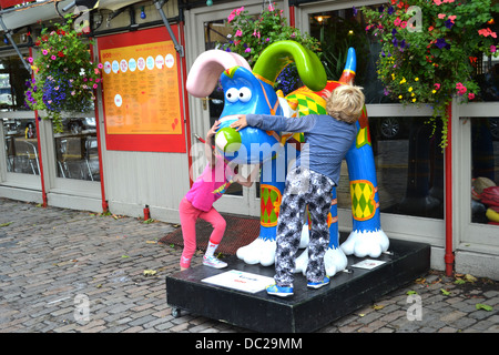 Two children (faces unseen) have fun crawling over a colorful model of Aarman Animations' character Gromit. - Stock Image