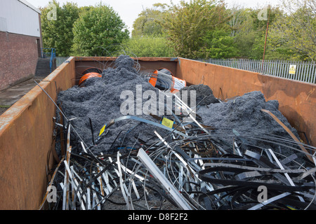 A large container full of scrap metal left over from product manufacturing - Stock Image