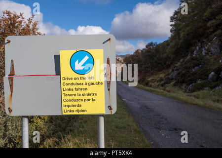 Sign in foreign languages reminding overseas tourists to drive on the left hand side of the road in the Scottish Higlands - Stock Image