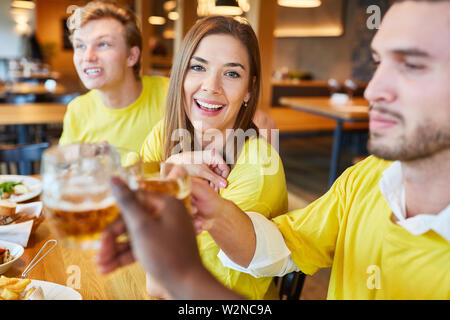 Friends as fans of a team while celebrating and drinking beer in a pub - Stock Image