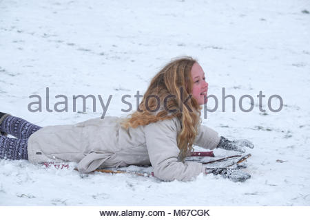 Nottingham, England, 1 March 2018 Girl sledging on slim body board in front of Wollaton Hall in snow from 'The - Stock Image