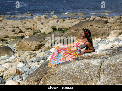 African Woman with Dreadlocks, and Wearing a Colourful Dress, Laying on Rocks by the Sea. - Stock Image