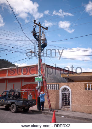 Electrical work crew change out a transformer in Nicaragua. - Stock Image