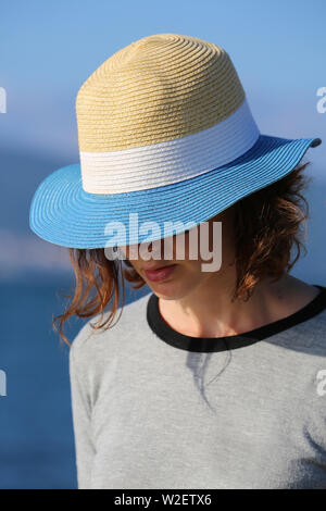 Mysterious Beautiful Woman In Straw Hat At The Beach. Close Up Portrait - Stock Image