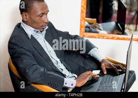 Young businessman works with his laptop in a clothing store. - Stock Image