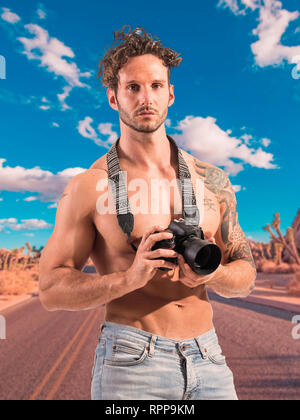 Shirtless man with professional photo camera in desert - Stock Image