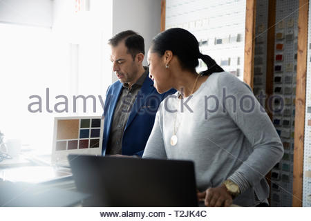 Interior designers working at laptop in office - Stock Image