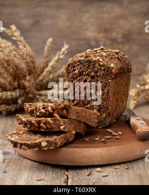 bread with seeds on old wooden background in a rustic style - Stock Image