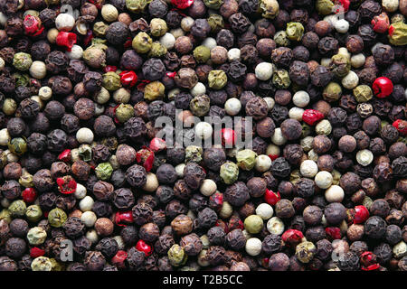 Mixed peppercorns background. Different colored peppercorns, close up. - Stock Image