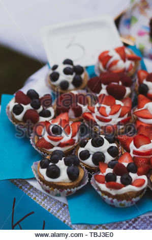 Fresh baked sweet cakes with strawberries and - Stock Image