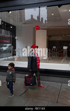 Shoppers walk past a window display that is part of a design theme called 'State of the Arts', at the Selfridges department store on Oxford Street, on 4th March 2019, in London England. State of the Arts is a gallery of works by nine crtically-acclaimed artists in Selfridges windows to celebrate the power of public art. Each of the artists are involved in creating a site-specific artwork at one of the new Elizabeth line stations as part of the Crossrail Art Programme. - Stock Image