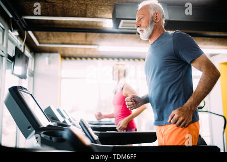 Senior people running on a treadmill in health club. - Stock Image