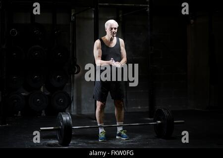 Senior man chalking hands for weightlifting in dark gym - Stock Image