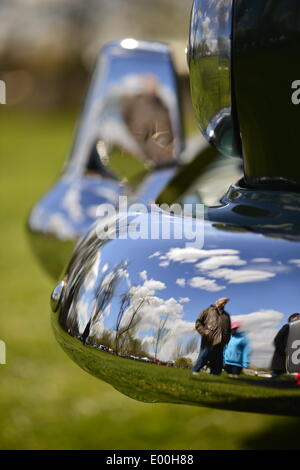 Floral Park, New York, U.S. 27th April, 2014. A green 1953 Dodge Coronet Diplomat front chrome upright and bumper reflect visitors and beautiful blue sky  at the 35th Annual Antique Auto Show at Queens Farm. Credit:  Ann E Parry/Alamy Live News - Stock Image