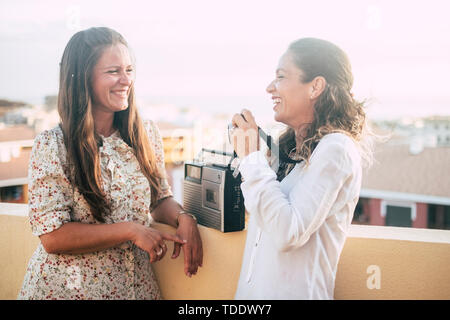 Couple of women happy friends smile and have fun laughing a lot together outdoor on the terrace at home - beautiful city view and nice pretty people t - Stock Image