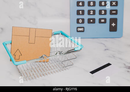 mini cardboard delivery parcel box into shopping basket with payment card and huge calculator in the background, concept of online shopping budget - Stock Image