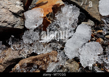Small ice blocks lie among fresh shards of rock on the shore of a glacial lake in Fitzroy, Argentina - Stock Image