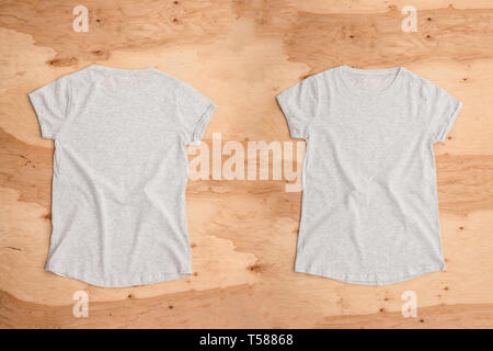 Front and back of light grey melange empty T-shirt on wooden background. Horizontal view. - Stock Image