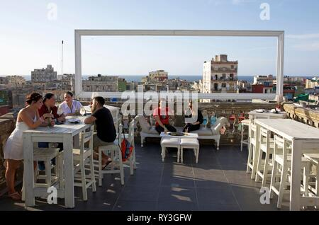 Cuba, La Havana, Centro Habana, young people on the terrace of the bar in rooftop of the paladar la Guarida, the Havana's most famous private restaurant, open on the rooftops of the city and the ocean - Stock Image