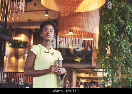 African American business woman stands with a folder in her hands - Stock Image
