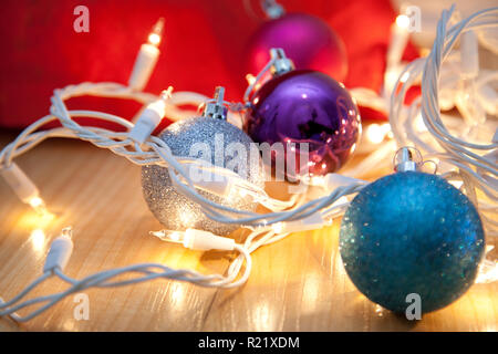 Blue, silver and purple christmas ornaments entangled in white lights - Stock Image