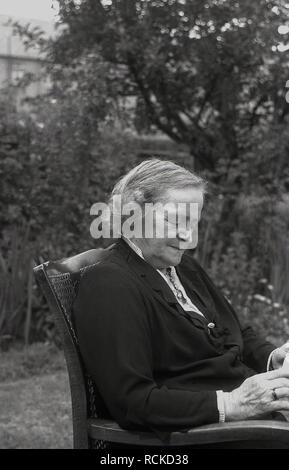 1950s, historical, elderly lady sitting reading in a garden, England, UK. - Stock Image
