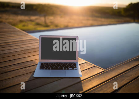 Laptop on wooden plank - Stock Image