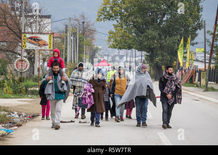 PRESEVO, SERBIA - OCTOBER 24, 2015: Family in front of a crowd of refugees on their way to register and enter Serbia at the border with Macedonia on B - Stock Image