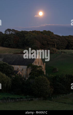 an old English barn under the full moon - Stock Image