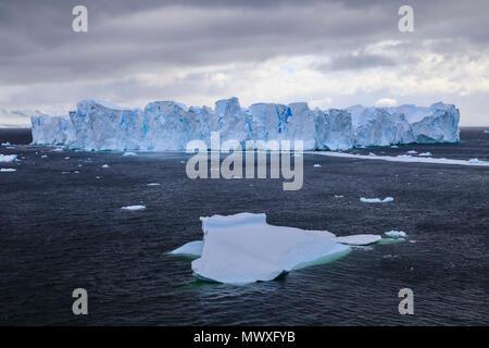 Large blue tabular iceberg, small iceberg and coast of Errera Channel, Danco Coast, Antarctic Peninsula, Antarctica, Polar Regions - Stock Image