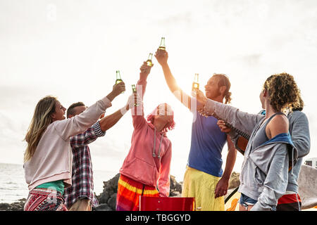 Group of friends making party and toasting with beers at sunset - Young happy people having fun at barbecue dinner outdoor - Stock Image