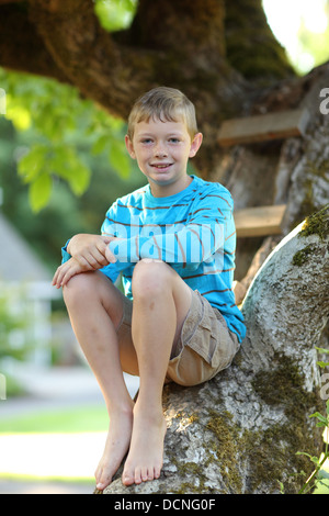Portrait of young boy sitting in tree - Stock Image