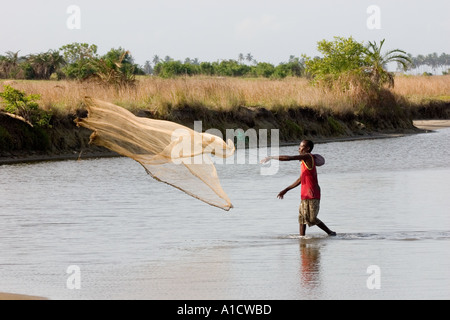 Fisherman throwing a castnet in the Muni lagoon near Winneba Ghana - Stock Image
