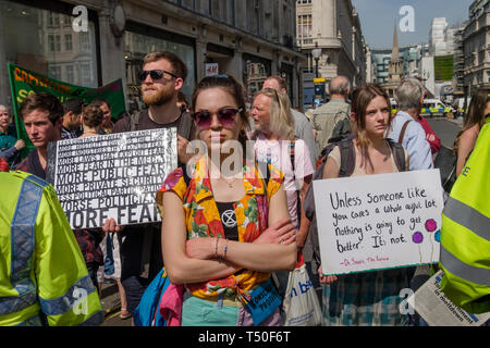 London, UK. 19th April 2019. People watch from outside the police cordon as police try to persuade protesters to leave by threatening them with arrest and begin cutting off those who were locked on around the bottom of the yacht. There were a number of arrests of protesters who refused to leave. A few tried to get the large crowd to protect the yacht, but XR organisers persuaded them not to physically oppose the police action. Peter Marshall/Alamy Live News - Stock Image