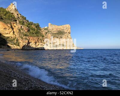 Late afternoon view over pebble beach to dramatic golden sea cliffs, Cala del Moraig, Benitachell, Costa Blanca, Spain - Stock Image