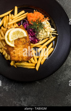 Pan fried fish with french fries and salad. Restaurant serving plate. - Stock Image